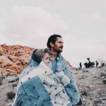 Image of a man and woman wrapped up in a denim patchwork blanket, with a desert backdrop