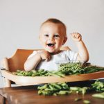 A baby sitting in a high chair with loads of raw peas in pods