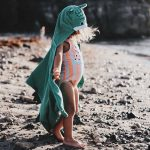 Photo of a little girl wearing a colourful swimming costume on the beacg
