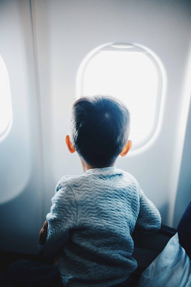 Little boy staring out of a plane window